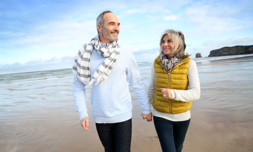 Over 50s couple walking on the beach: life insurance comparison